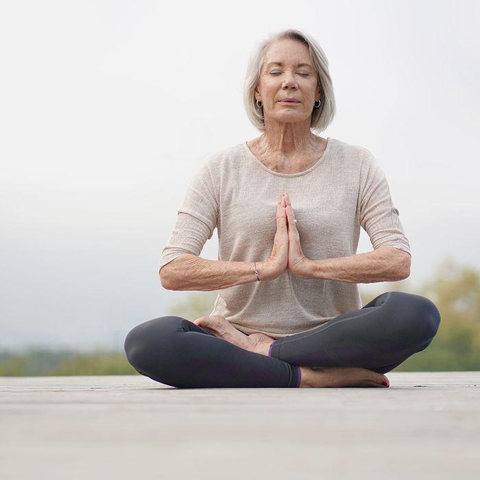 Ältere Frau beim Meditieren an der frischen Luft